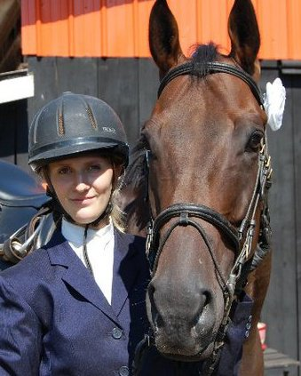 Krystal is posing with her young training horse after her graduation ride