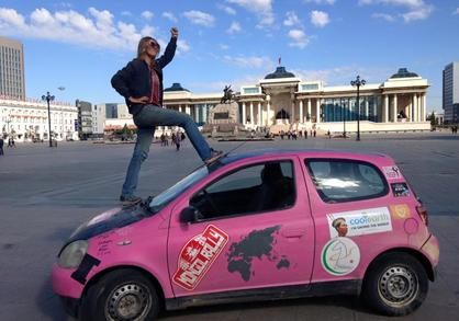 Krystal posing triumphant on the hood of the Pink Yak in Mongolia
