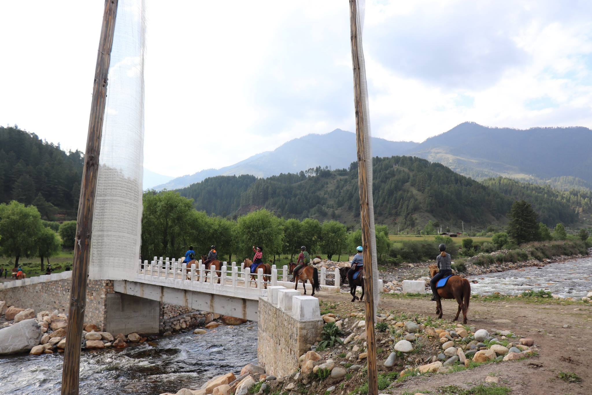 Riders are crossing a bridge behind a couple of prayer flags while horse riding in Bhutan