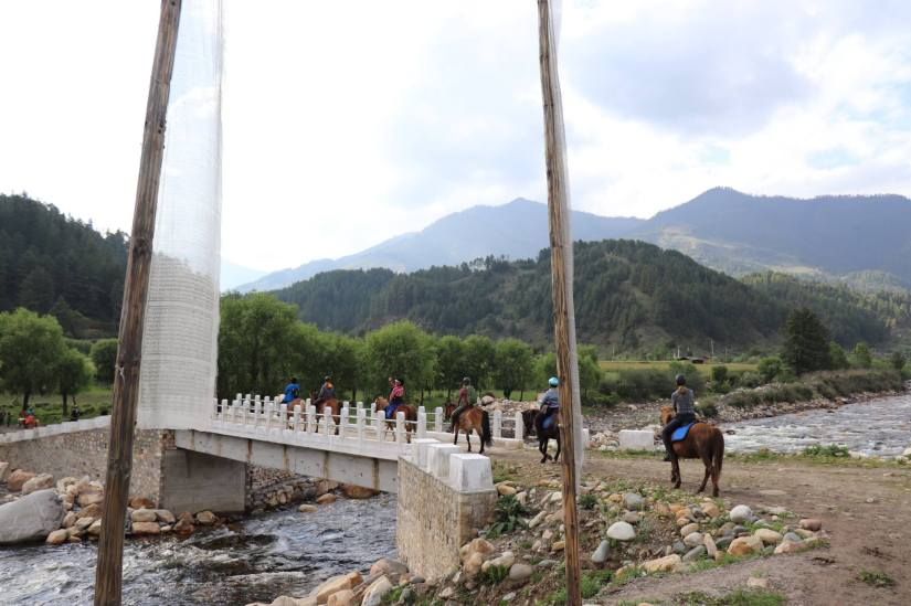 Riders in Bhutan crossing a bridge behind a couple of prayer flags