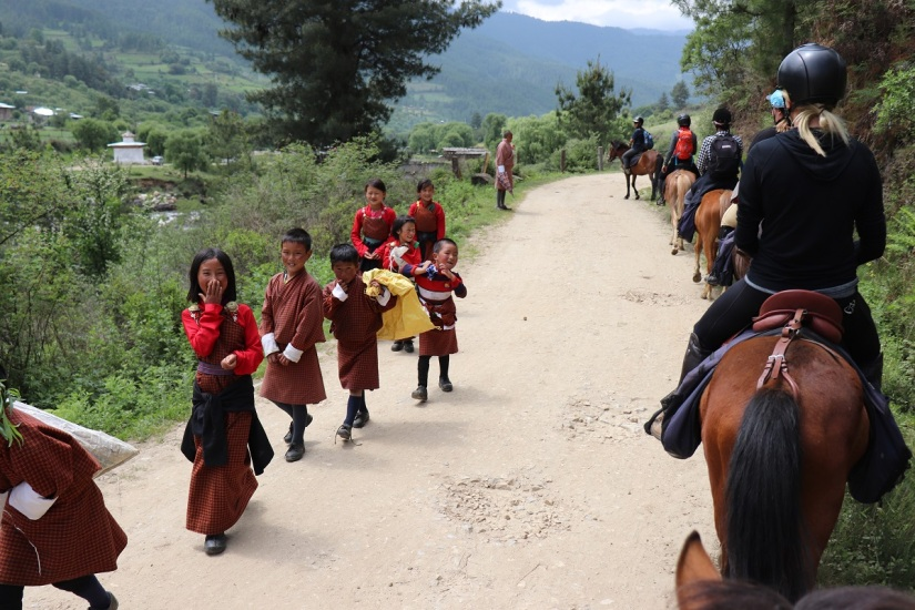 The riders on their Bhutanese mountain ponies are passing a group of children