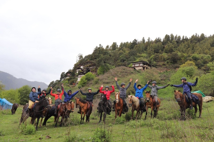 A group of Riders on Bhutanese mountain ponies in front of a temple
